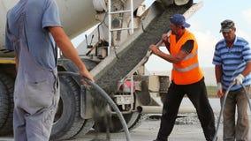 Χύνοντας τσιμέντο φορτηγών τσιμέντου σε μια κατασκευή διαδρόμων φιλμ μικρού μήκους