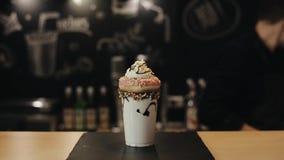 Χύνοντας υγρή σοκολάτα και τοποθέτηση ενός φραγμού γκοφρετών σοκολάτας στο ακραίο milkshake με ρόδινο doughnut και κτυπημένη μια  απόθεμα βίντεο
