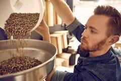 Χύνοντας φασόλια καφέ ατόμων σε μια ψήνοντας μηχανή Στοκ Φωτογραφίες
