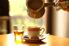 Χύνοντας φλιτζάνι του καφέ Στοκ Εικόνες