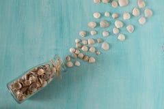 Χύσιμο θαλασσινών κοχυλιών από το γυαλί μπουκαλιών στο μπλε υπόβαθρο Στοκ Εικόνα