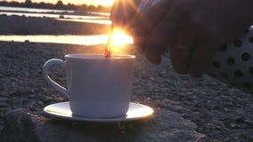 Χύστε ένα εύγευστο καυτό τσάι ή έναν καφέ από τον ποταμό στο ηλιοβασίλεμα σε ένα άσπρο φλυτζάνι από ένα μπουκάλι thermos σε αργή  απόθεμα βίντεο