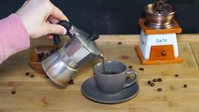 Χύστε ένα φλιτζάνι του καφέ από τον κατασκευαστή καφέ moka, ατμός από τον καφέ απόθεμα βίντεο
