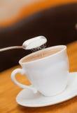 Χύστε τη ζάχαρη στον καφέ γάλακτος του κλασσικού άσπρου φλυτζανιού Στοκ φωτογραφίες με δικαίωμα ελεύθερης χρήσης