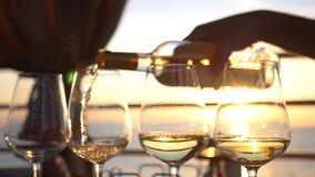 Χύστε το νόστιμο άσπρο κρασί στα ποτήρια γυαλιού με μια αντανάκλαση του ηλιοβασιλέματος και τη θάλασσα σε τους HD, 1920x1080 κίνη απόθεμα βίντεο