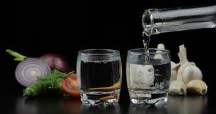 Χύστε το οινόπνευμα πίνει τη βότκα από το μπουκάλι στα πυροβοληθε'ντα γυαλιά Υπόβαθρο με τα λαχανικά στοκ εικόνα με δικαίωμα ελεύθερης χρήσης