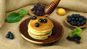 Χύστε το φρέσκο μέλι σε έναν σωρό της τηγανίτας με το βακκίνιο στο ξύλινο κύπελλο και τα τροπικά φρούτα απόθεμα βίντεο
