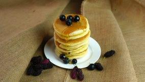 Χύστε το φρέσκο μέλι στον πύργο των τηγανιτών στο άσπρο πιάτο στο ύφασ απόθεμα βίντεο