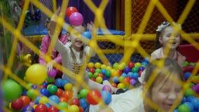 Χώρος για παιχνίδη παιδιών Τα παιδιά παίζουν σε μια ξηρά λεκάνη που γεμίζουν με χρωματισμένες τις πλαστικό σφαίρες απόθεμα βίντεο