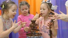 Χώρος για παιχνίδη παιδιών Τα παιδιά τρώνε τη σοκολάτα από μια πηγή σοκολάτας απόθεμα βίντεο