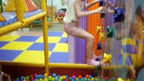 Χώρος για παιχνίδη παιδιών Το παιδί αναρριχείται στον τοίχο ενός τοίχου αναρρίχησης απόθεμα βίντεο