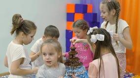 Χώρος για παιχνίδη παιδιών ` s Τα παιδιά τρώνε τη σοκολάτα από μια πηγή σοκολάτας απόθεμα βίντεο