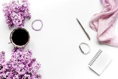 Χώρος εργασίας με τα lilic λουλούδια και καφές για τη γυναίκα στο άσπρο γραφείων πρότυπο άποψης υποβάθρου τοπ Στοκ φωτογραφία με δικαίωμα ελεύθερης χρήσης