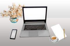 Χώρος εργασίας με το έξυπνο τηλεφωνικό άσπρο κενό έγγραφο lap-top και μάνδρα με το τσάι πρωινού που απομονώνεται Στοκ Φωτογραφία