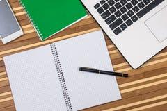 Χώρος εργασίας με το κενά σημειωματάριο, το lap-top και το τηλέφωνο στο γραφείο στοκ φωτογραφία με δικαίωμα ελεύθερης χρήσης