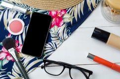 Χώρος εργασίας με το smartphone, eyeglasses, πρόχειρα φαγητά, καπέλο ήλιων και cosme Στοκ φωτογραφία με δικαίωμα ελεύθερης χρήσης
