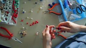 Χώρος εργασίας του καλλιτέχνη εξαρτημάτων που κάνει τα σκουλαρίκια χαντρών, άποψη άνωθεν απόθεμα βίντεο