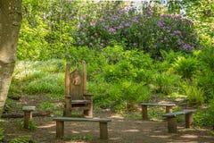 Χώρος συνάντησης του Glen νεράιδων με τις ξύλινες χαρασμένες έδρες και από την πρασινάδα του Forrest στη νεράιδα Glen Fullarton κ στοκ φωτογραφία με δικαίωμα ελεύθερης χρήσης