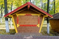 Χλεύη αφισών επάνω του κενού ξύλινου στάβλου αγοράς οδών στο πεζοδρόμιο Φύλλωμα φθινοπώρου γύρω Χρυσά και πράσινα φύλλα Στοκ εικόνες με δικαίωμα ελεύθερης χρήσης
