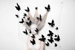 Χλωμή γυναίκα στο κουκούλι με τις πεταλούδες Στοκ Φωτογραφίες