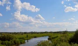 Χλόη λιβαδιών ποταμών τομέων του χωριού σπιτιών πρωινού φύσης σύννεφων σύννεφων τοπίων ουρανού στοκ εικόνες