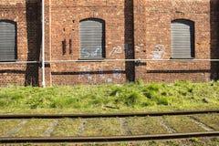 Χλόη σιδηροδρόμου φορτηγών τρένων και σωλήνες και γκράφιτι στο παλαιό τούβλο Στοκ φωτογραφίες με δικαίωμα ελεύθερης χρήσης