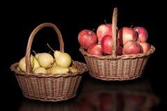 Ψάθινα καλάθια με τα μήλα και αχλάδια στο καθαρό μαύρο υπόβαθρο Στοκ φωτογραφίες με δικαίωμα ελεύθερης χρήσης
