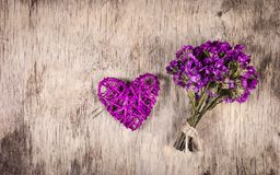 Ψάθινες καρδιά και ανθοδέσμη των wildflowers Ρόδινος βαλεντίνος σε ένα ξύλινο υπόβαθρο Στοκ Εικόνες