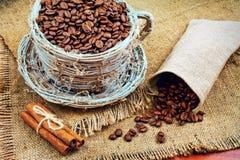 Ψάθινη κούπα με τα φασόλια καφέ και κανέλα σε ένα υπόβαθρο της γιούτας Στοκ Εικόνα