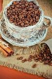 Ψάθινη κούπα με τα φασόλια καφέ σε ένα υπόβαθρο της γιούτας Στοκ εικόνα με δικαίωμα ελεύθερης χρήσης