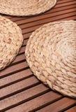 Ψάθινη στρογγυλή στάση στον πίνακα από τους ξύλινους φραγμούς Στοκ Φωτογραφία