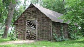 Ψάθινο αγροτικό κτήριο στα αλσύλλια των δέντρων απόθεμα βίντεο