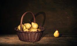 Ψάθινο καλάθι με τα αχλάδια και ένα αχλάδι στον πίνακα, σκοτεινό υπόβαθρο ζωγραφικής Στοκ φωτογραφία με δικαίωμα ελεύθερης χρήσης