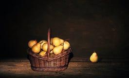 Ψάθινο καλάθι με τα αχλάδια και ένα αχλάδι στον πίνακα, σκοτεινό υπόβαθρο ζωγραφικής Στοκ εικόνες με δικαίωμα ελεύθερης χρήσης