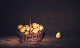 Ψάθινο καλάθι με τα αχλάδια και ένα αχλάδι στον πίνακα, σκοτεινό υπόβαθρο ζωγραφικής Στοκ φωτογραφίες με δικαίωμα ελεύθερης χρήσης