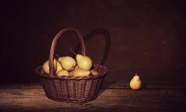 Ψάθινο καλάθι με τα αχλάδια και ένα αχλάδι στον πίνακα, σκοτεινό υπόβαθρο ζωγραφικής Στοκ Εικόνες