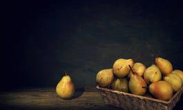 Ψάθινο καλάθι με τα αχλάδια και ένα αχλάδι στον πίνακα, σκοτεινό υπόβαθρο ζωγραφικής Στοκ εικόνα με δικαίωμα ελεύθερης χρήσης