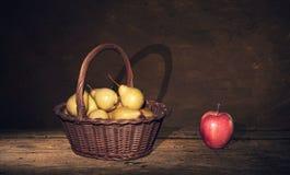 Ψάθινο καλάθι με τα αχλάδια και ένα μήλο στον πίνακα, σκοτεινό υπόβαθρο ζωγραφικής Στοκ Φωτογραφία