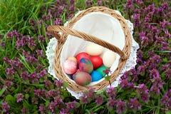 Ψάθινο καλάθι με τα ζωηρόχρωμα αυγά Πάσχας Στοκ Εικόνες