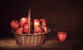 Ψάθινο καλάθι με τα μήλα και ένα μήλο στον πίνακα, σκοτεινό υπόβαθρο ζωγραφικής Στοκ εικόνα με δικαίωμα ελεύθερης χρήσης
