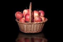 Ψάθινο καλάθι με τα μήλα στο μαύρο υπόβαθρο Στοκ φωτογραφίες με δικαίωμα ελεύθερης χρήσης