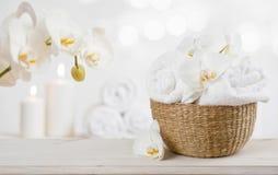 Ψάθινο καλάθι με τις πετσέτες SPA στον πίνακα πέρα από το αφηρημένο υπόβαθρο Στοκ Φωτογραφίες