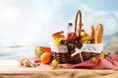 Ψάθινο καλάθι πικ-νίκ με τα τρόφιμα στον πίνακα στην παραλία Στοκ Φωτογραφία
