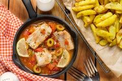 Ψάρια βακαλάων που μαγειρεύονται στη σάλτσα ντοματών με τις ελιές, το λεμόνι και την ντομάτα στοκ φωτογραφία με δικαίωμα ελεύθερης χρήσης