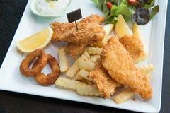 Ψάρια και τσιπ που εξυπηρετούνται με την κρέμα και τα λαχανικά Στοκ Εικόνες