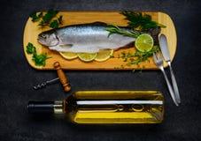 Ψάρια πεστροφών και μπουκάλι του άσπρου κρασιού Στοκ Εικόνες