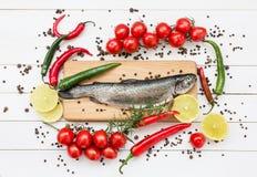 Ψάρια πεστροφών στον ξύλινο τέμνοντα πίνακα με τις ντομάτες κερασιών Στοκ Φωτογραφίες