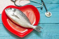Ψάρια στο κόκκινα πιάτο και το στηθοσκόπιο καρδιών Στοκ Εικόνα