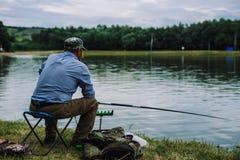 Ψάρια συλλήψεων ατόμων με μια ράβδο αλιείας Στοκ Φωτογραφίες