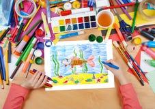 Ψάρια σχεδίων παιδιών υποβρύχια και βυθός, τοπ χέρια άποψης με την εικόνα ζωγραφικής μολυβιών σε χαρτί, εργασιακός χώρος έργου τέ Στοκ Εικόνα